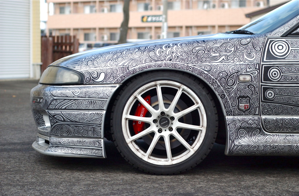 woman draws designs on car with sharpie