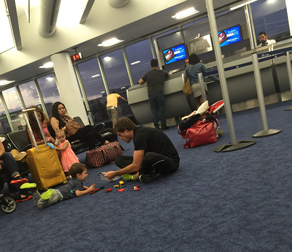 dad playing cars with son airport delay