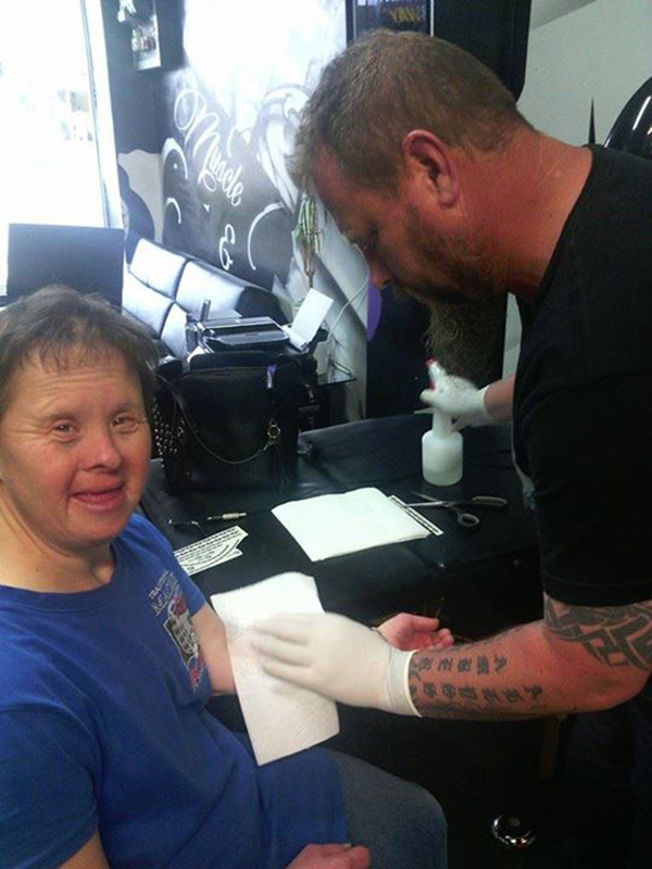tattoo artist puts temporary tattoos on woman