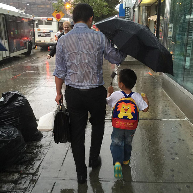 being a dad holding umbrella for kid while getting wet
