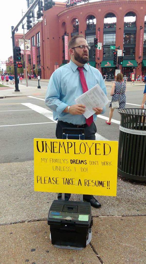 unemployed man with resumes outside of stadium