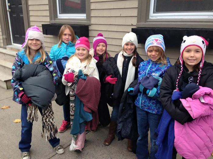 kids hanging coats for homeless