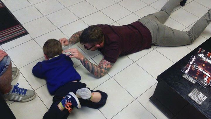 barber cuts hair on floor of boy with autism