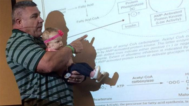 Baylor professor teaches class holding baby