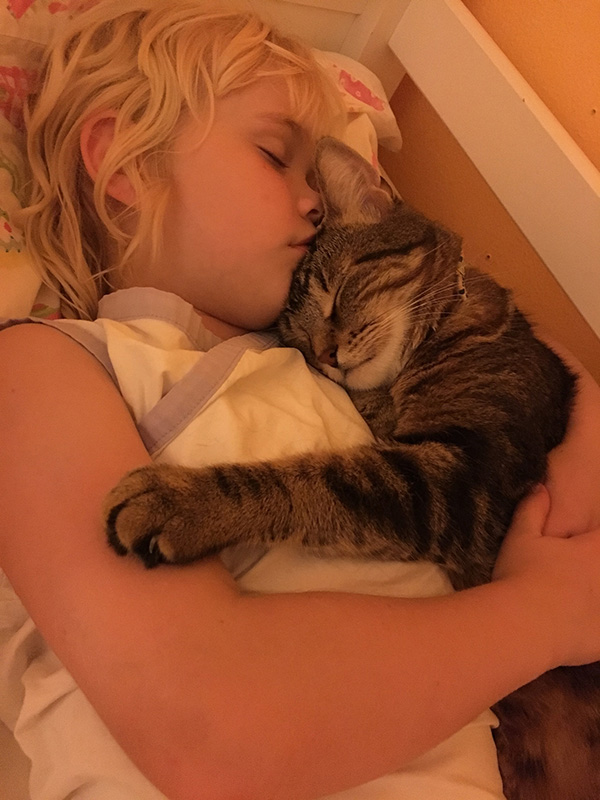 girl snuggling with cat