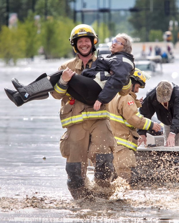 firefighter smiling carrying old woman