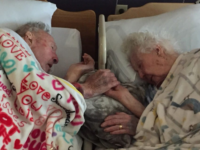 100 year old grandpa holds wifes hand
