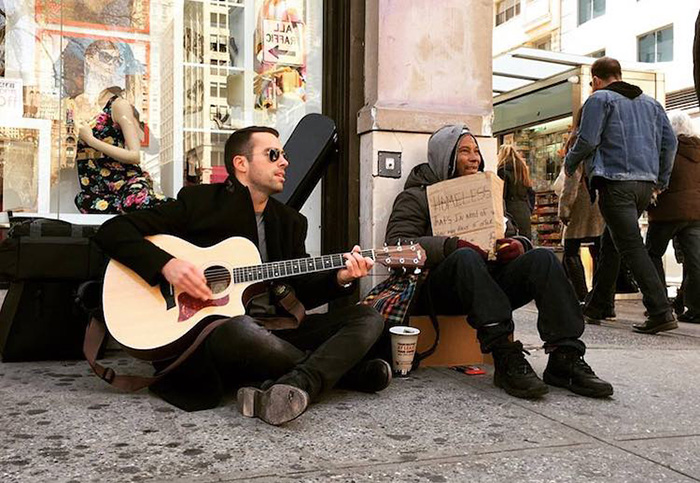 man plays guitar near homeless people to help them get money