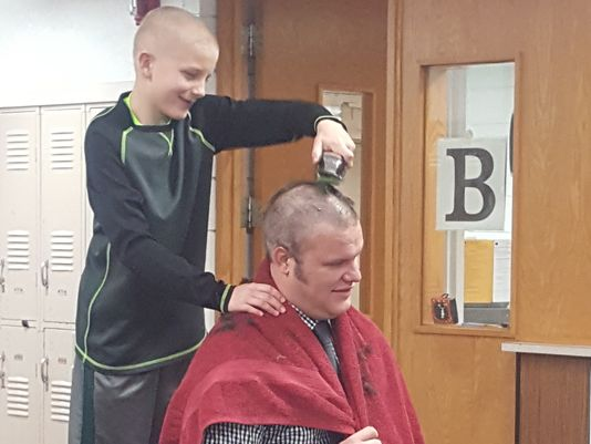 principal shaves head for bald student
