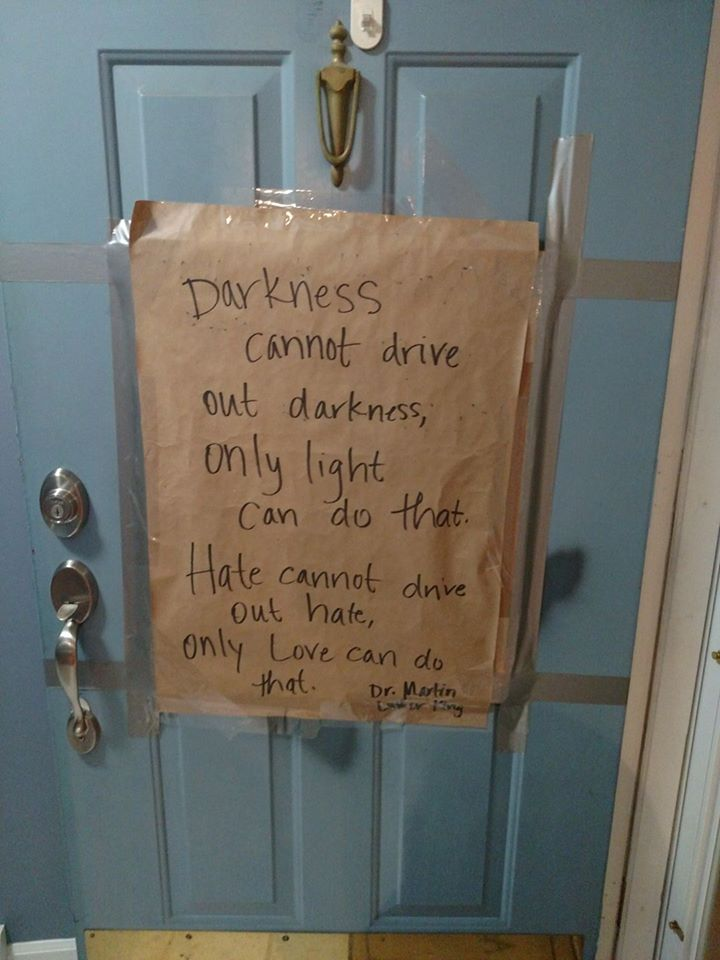 woman battles hate with love swastika on door quotes