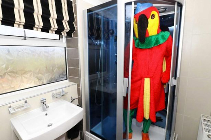man dressed as parrot sells home