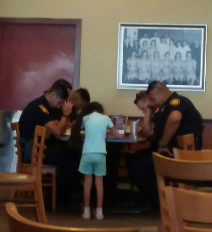 little girl prays with police officers