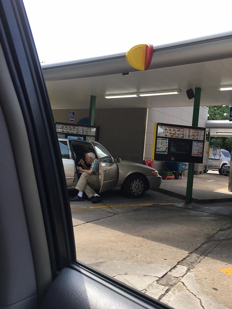 elderly man feeding wife ice cream in car