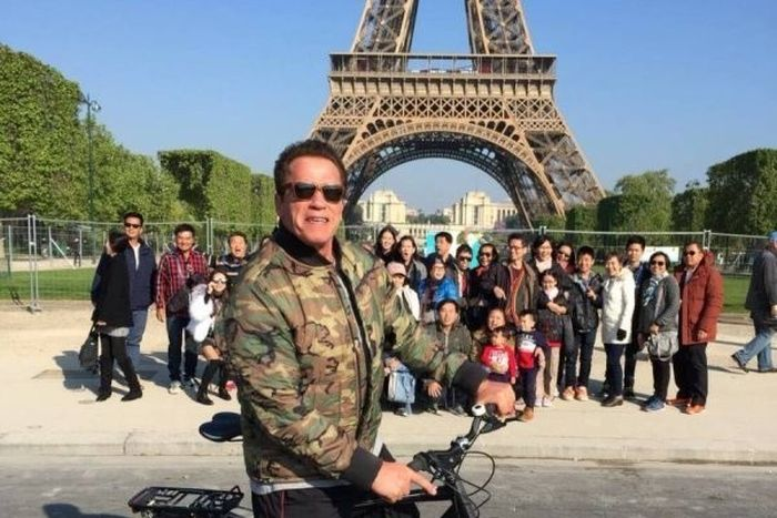 arnold photobombs tourists Eiffel tower