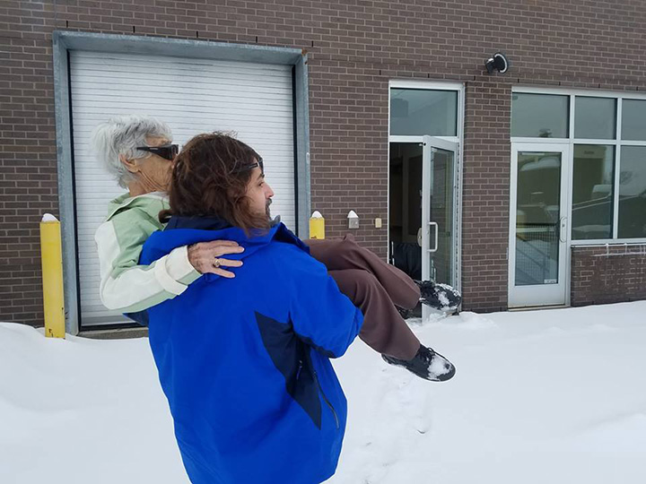 doctor carries elderly patient in the snow