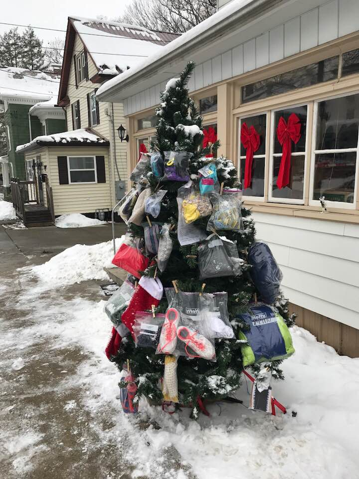 Christmas tree outside with supplies for the needy