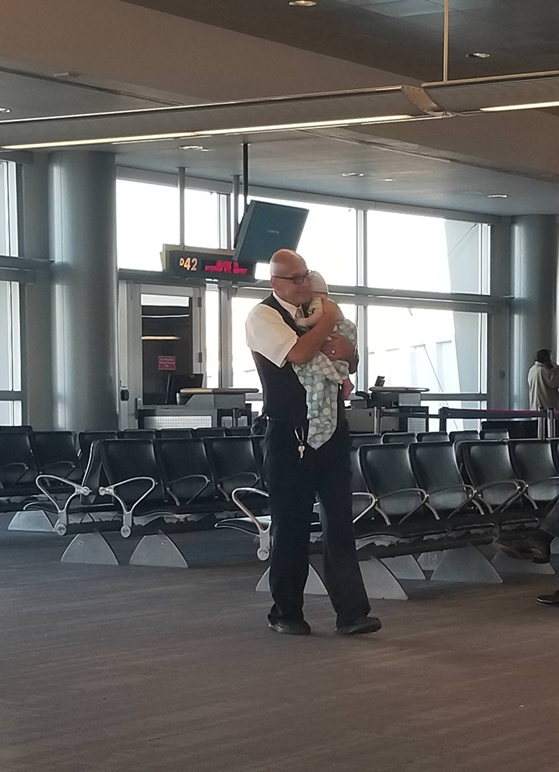 airport employee holds crying baby for mom traveling alone