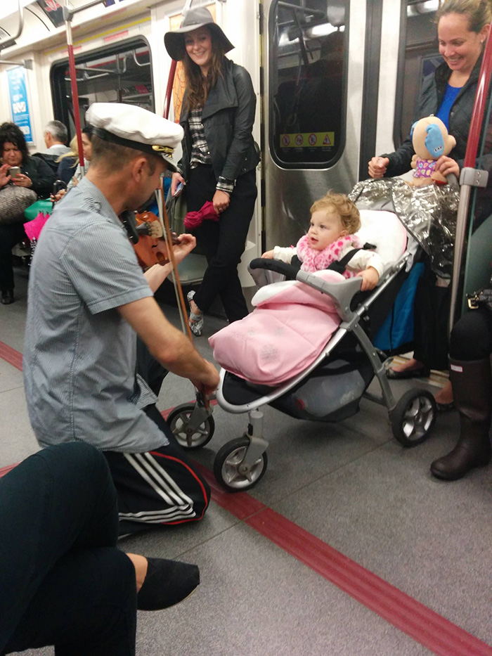 man plays violin for crying baby on subway