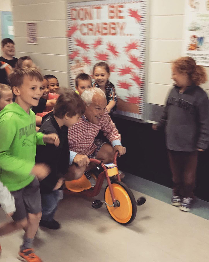 principal challenges kids to read with tricycle push