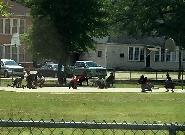 young boys playing basketball kneel for funeral procession