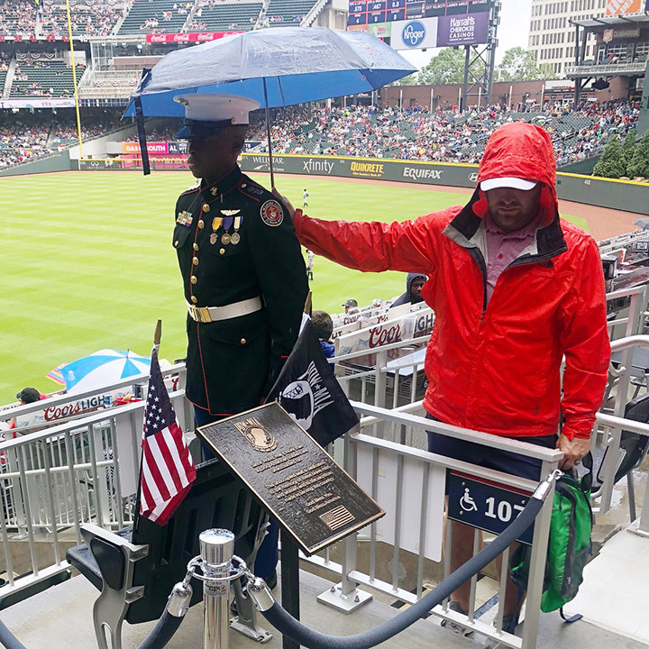 man holds umbrella over military man Braves game
