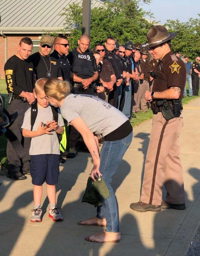 70 police officers welcome boy back to school who lost dad in line of duty