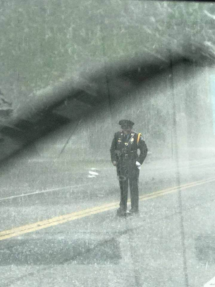 police officer stands over turtle in rain Sharnise Hawkins