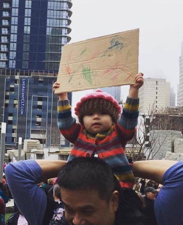 toddler holding up sign of scribbles