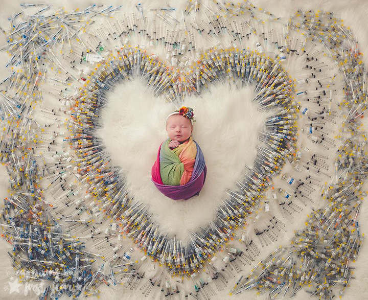 baby surrounded by IVF syringes