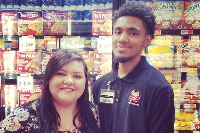 grocery store employee lets boy with autism help him stock shelves