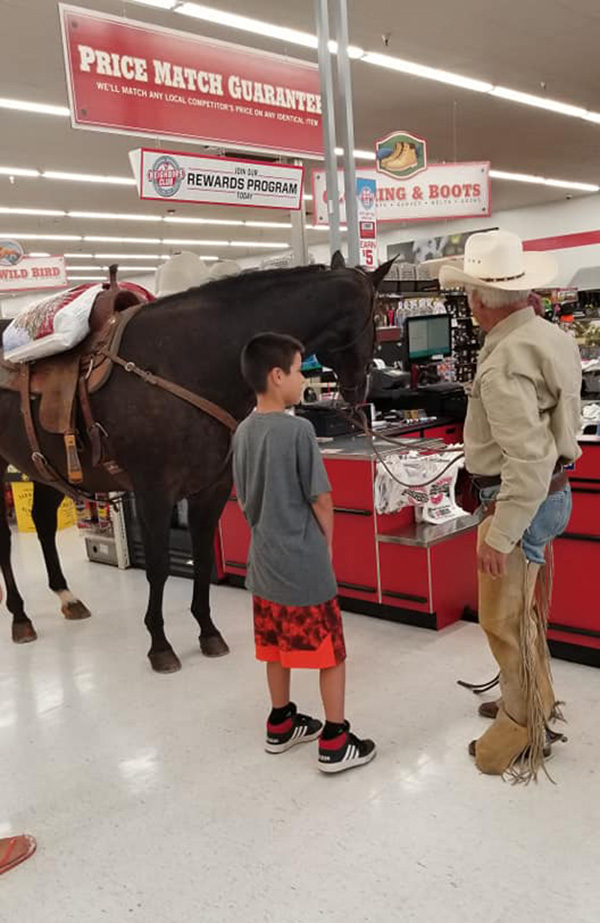 man brings horse in tractor supply store