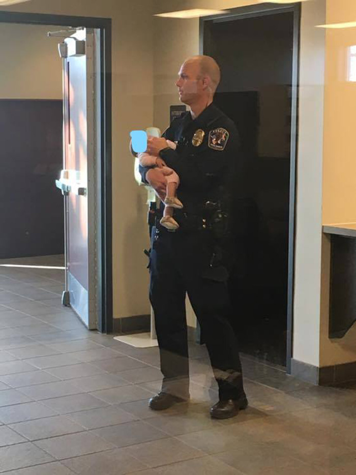 police officer holds baby for mom