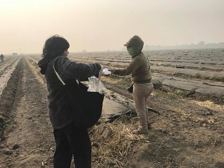 woman hands out masks to farm workers California