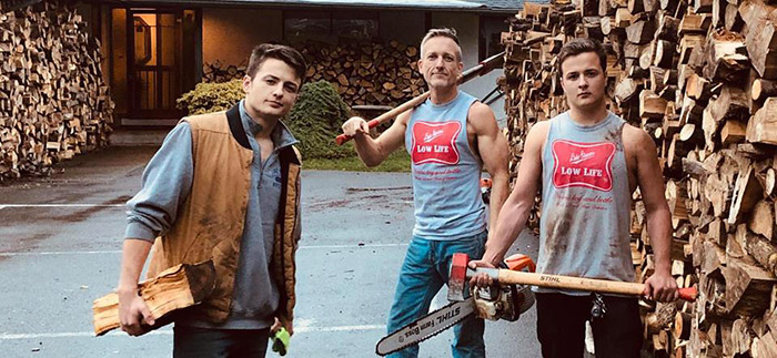 father and sons chop wood for needy