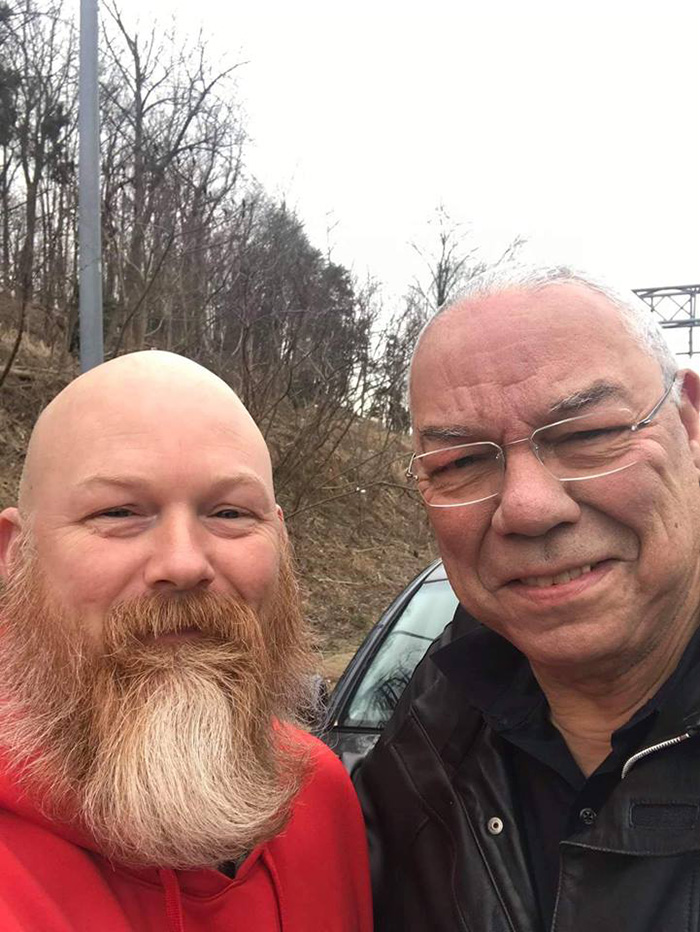 man helps general Powell on highway car tire