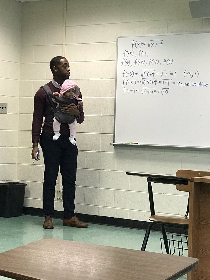 professor holds baby in class