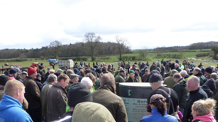 farmers stand in silence at auction
