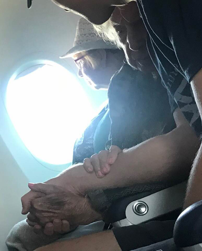man comforts elderly woman on plane