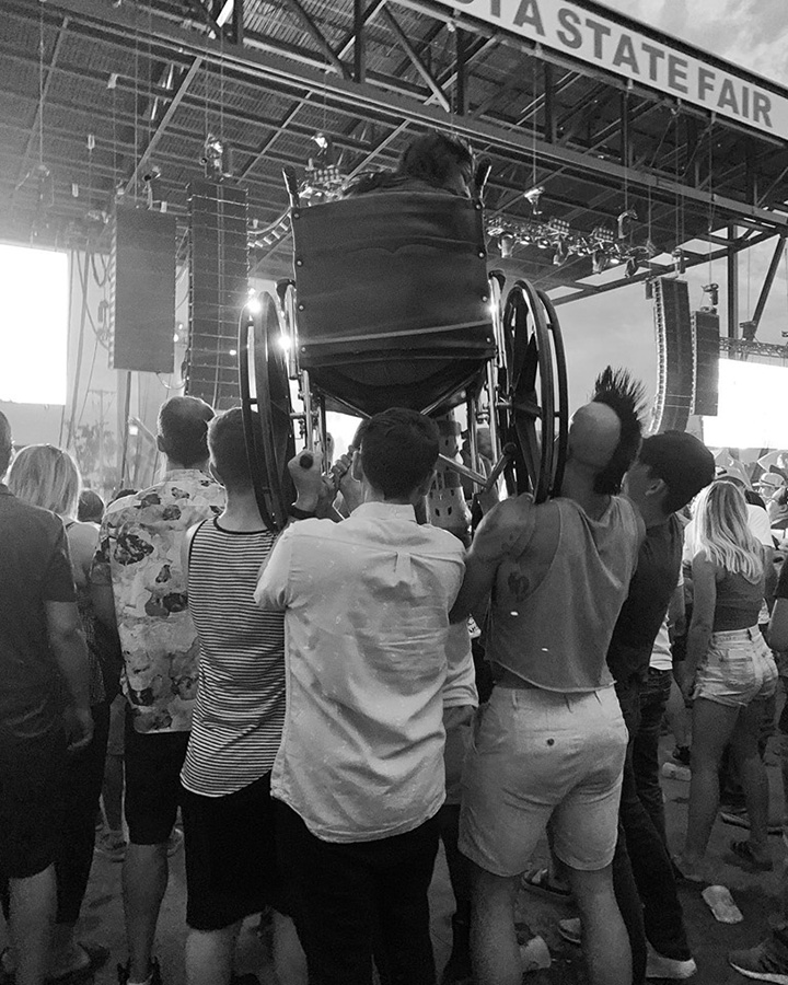 crowd holds up fan in wheelchair at weezer concert