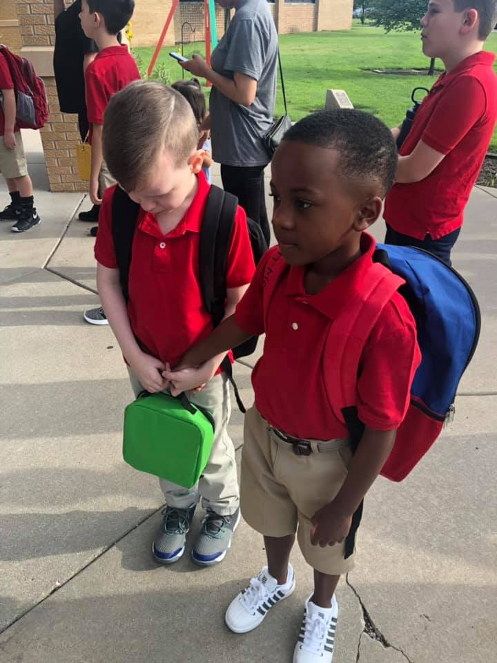 boy holds hand of crying kid first day of school