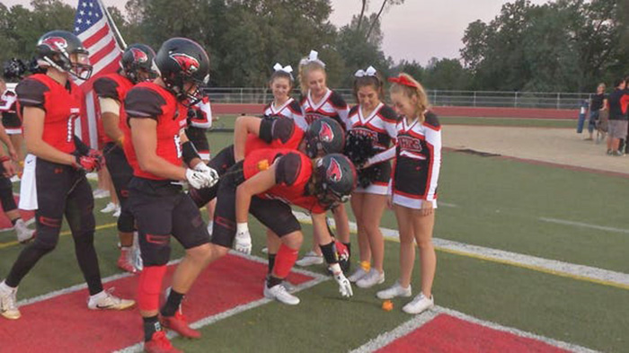 football team supports cheerleader cancer roses