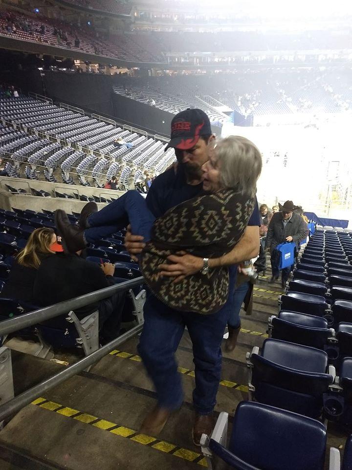 man carries woman to seat in stadium