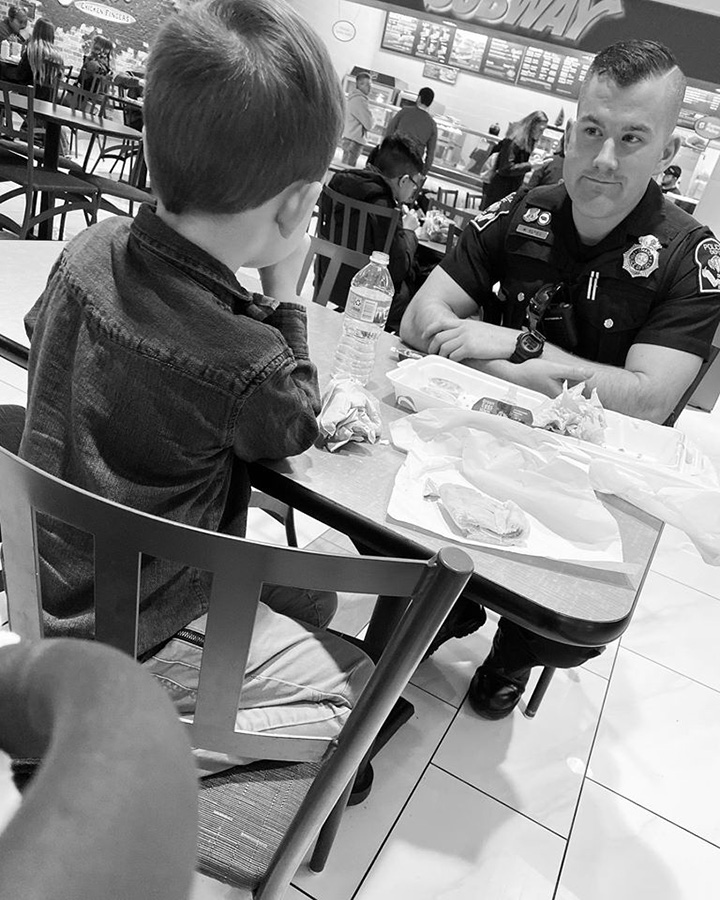 boy quits playing to eat with cop sitting alone