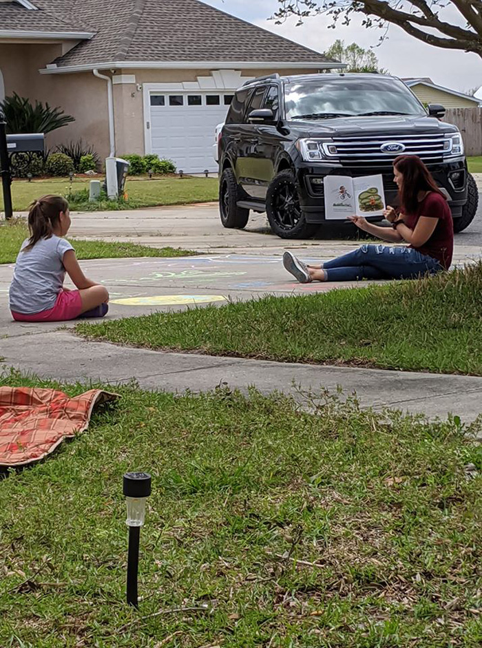 teacher reads to students in driveway