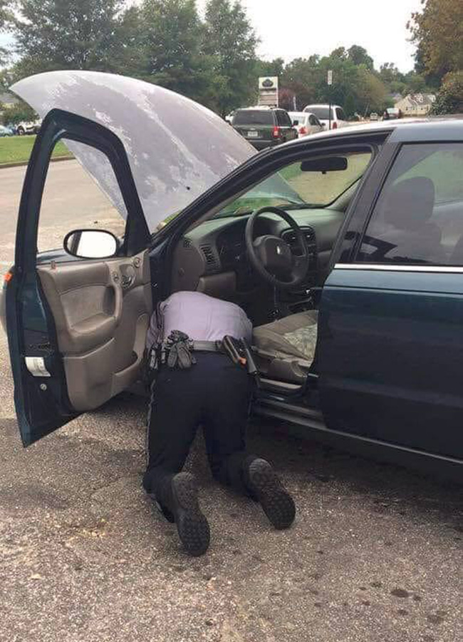 police officer helps fix car