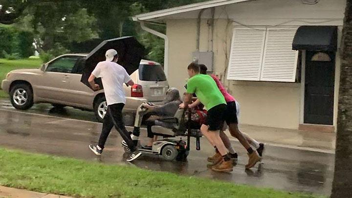 boys push woman in wheelchair in the rain